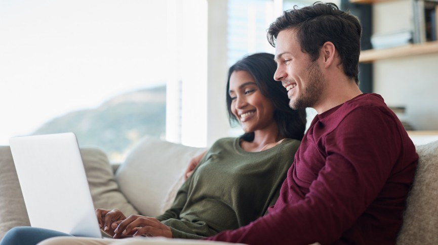 couple sitting at home looking at a laptop